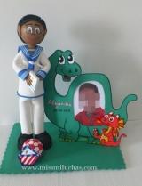 Alejandro aparece vestido con su traje de Primera Comunión, y su fotografía en un marco de fotos con forma de dinosaurio, su animal favorito.