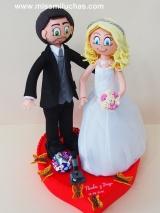 Paula y Diego aparecen sobre un corazón con mariposas, para coronar su tarta nupcial.